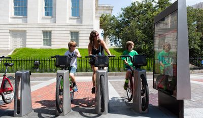 Marti Coogan and her sons Zachary and Aaron, from Bel Air, MD, rest on bikes at the Capital Bikeshare stand outside the National Portrait Gallery Monday morning. Keith Lane/Special to the Washington TImes.