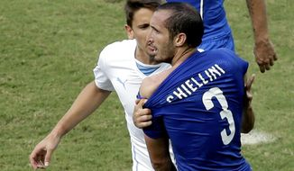 Italy's Giorgio Chiellini complains after Uruguay's Luis Suarez ran into his shoulder with his teeth during the group D World Cup soccer match between Italy and Uruguay at the Arena das Dunas in Natal, Brazil, Tuesday, June 24, 2014. (AP Photo/Hassan Ammar)