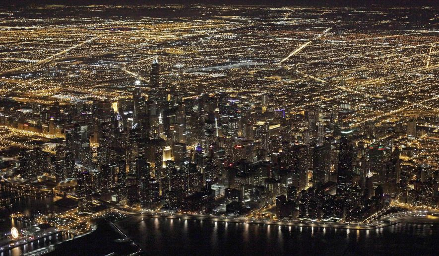 This Sunday, Nov. 24, 2013, file photo, shows an aerial view at night of the downtown Chicago skyline. (AP Photo/Kiichiro Sato, File)