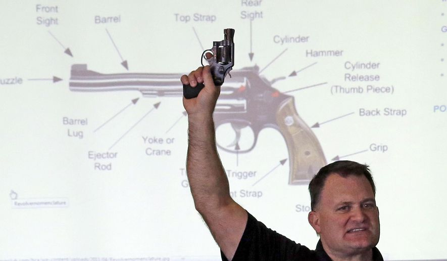 Clark Aposhian, president of Utah Shooting Sport Council, holds a pistol during concealed weapons training for 200 Utah teachers. (Associated Press/File)