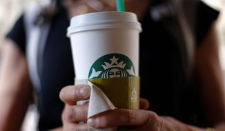 In this May 31, 2014 photo, a woman holds a coffee drink outside a Starbucks in downtown Chicago. Starbucks is raising prices on some of its drinks by 5 cents to 20 cents starting next week, and customers can also soon expect to pay $1 more for the packaged coffee it sells in supermarkets. Prices for medium and large brewed coffees, which are known as Grande and Venti, respectively, will go up between 10 cents and 15 cents in most U.S. markets, the company said.  (AP Photo/Gene J. Puskar)
