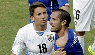 Italy's Giorgio Chiellini, right, shows his shoulder after colliding with Uruguay's Luis Suarez's mouth as Uruguay's Gaston Ramirez (18) watches during the group D World Cup soccer match between Italy and Uruguay at the Arena das Dunas in Natal, Brazil, Tuesday, June 24, 2014. (AP Photo/Hassan Ammar)