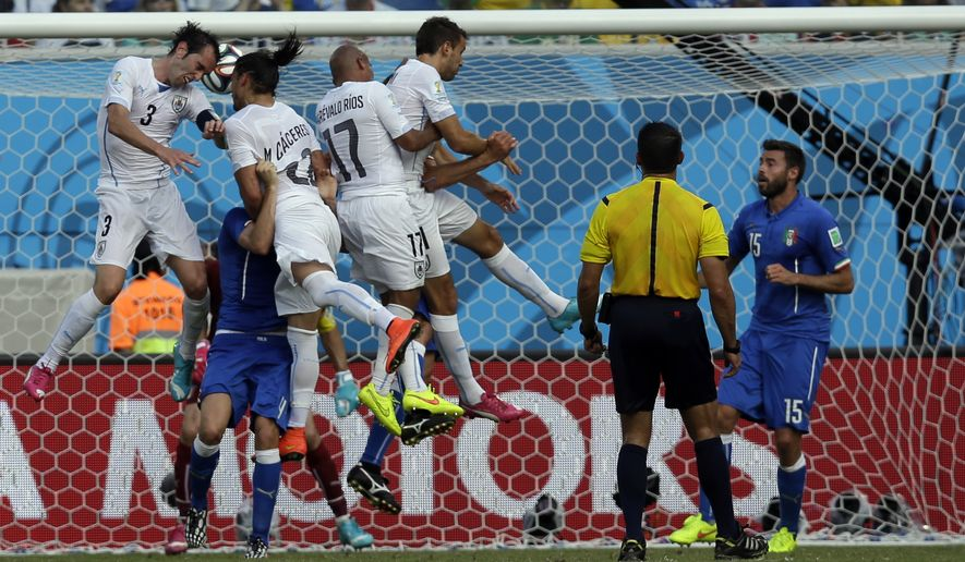 Uruguay's Diego Godin, left, scores the opening goal during the group D World Cup soccer match between Italy and Uruguay at the Arena das Dunas in Natal, Brazil, Tuesday, June 24, 2014. (AP Photo/Andrew Medichini)