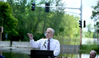 Minnesota Gov. Mark Dayton is surrounded by flood waters as he participated in a groundbreaking of a flood mitigation project, Tuesday, June 24, 2014 in  Chaska Minn. Dayton made the rounds of more Minnesota cities along flood-swollen rivers Tuesday to meet with emergency managers and local elected officials. (AP Photo/The Star Tribune, Elizabeth Flores)  MANDATORY CREDIT; ST. PAUL PIONEER PRESS OUT; MAGS OUT; TWIN CITIES LOCAL TELEVISION OUT
