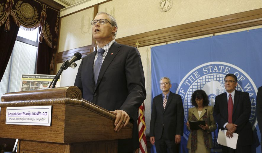 Gov. Jay Inslee, foreground, speaks to the media about public awareness and safety efforts the state is making in advance of the start of retail sales of recreational marijuana, on Tuesday, June 24, 2014 in Olympia, Wash. Inslee says that it's imperative that marijuana stays out of the hands of minors. (AP Photo/Rachel La Corte)