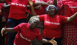 FILE - In this file photo taken on Tuesday, May 27, 2014, Women attend a prayer meeting calling on the government to rescue the kidnapped girls of the government secondary school in Chibok, in Abuja, Nigeria. Extremists have abducted 91 more people, including toddlers as young as 3, in weekend attacks on villages in Nigeria, witnesses said Tuesday, June 24, 2014, providing fresh evidence of the military's failure to curb an Islamic uprising and the government's inability to provide security. The victims included 60 girls and women, some of whom were married, and 31 boys, witnesses said. A local official confirmed the abductions, but security forces denied them. Nigeria's government and military have been internationally embarrassed by their slow response to the abductions of more than 200 schoolgirls who were kidnapped April 15 and remain captive. (AP Photo/Sunday Alamba,File)