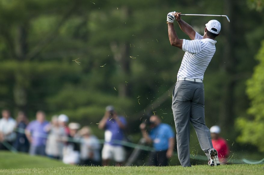 Tiger Woods plays his approach shot on the 16th hole during the pro-am at the Quicken Loans National golf tournament being played on Wednesday at Congressional Country Club in Bethesda, Maryland.