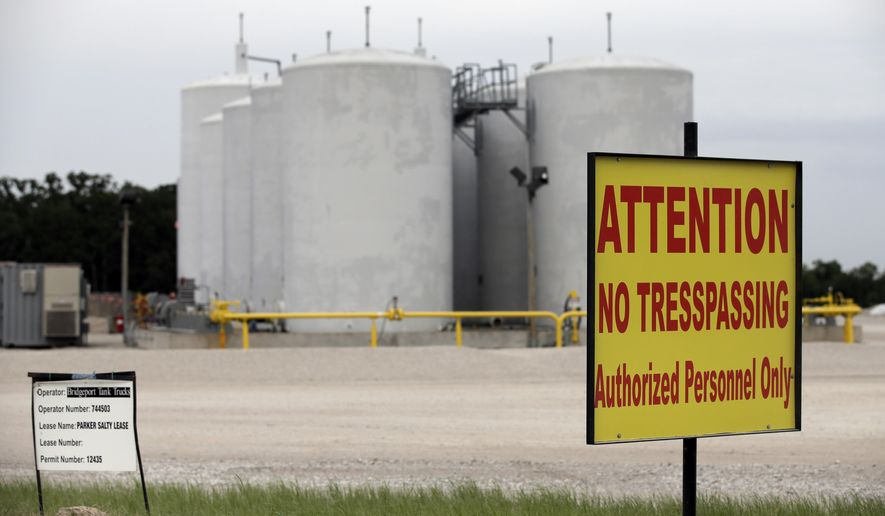 Signs warn against trespassing at a well injection site operated by Bridgeport Tank Trucks LTD., Saturday, June 21, 2014, in Azle, Texas. Earthquakes used to be unheard of on the vast stretches of prairie that unroll across Texas and Oklahoma.  But in recent years, temblors have become commonplace. Oklahoma recorded 145 of them just between January and the start of May. (AP Photo/Tony Gutierrez)