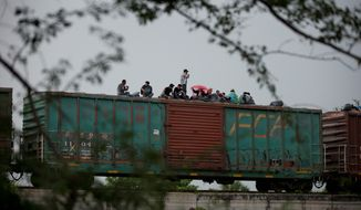 Migrants wait atop the freight train they had been traveling north on, as it starts to rain after the train suffered a minor derailment outside Reforma de Pineda, Chiapas state, Mexico. Migrants from Guatemala, Honduras and El Salvador travel north by train, by foot, or if they can afford it, by bus. Along the way, they face attacks by criminal gangs and extortion by Mexican authorities. (Associated Press)