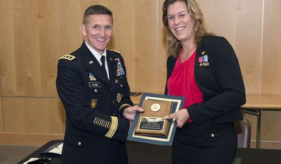 Retired Navy SEAL Kristin Beck receives a plaque from DIA Director Lt. Gen. Michael Flynn following the agency's Pride Month event on June 18. (dia public affairs)