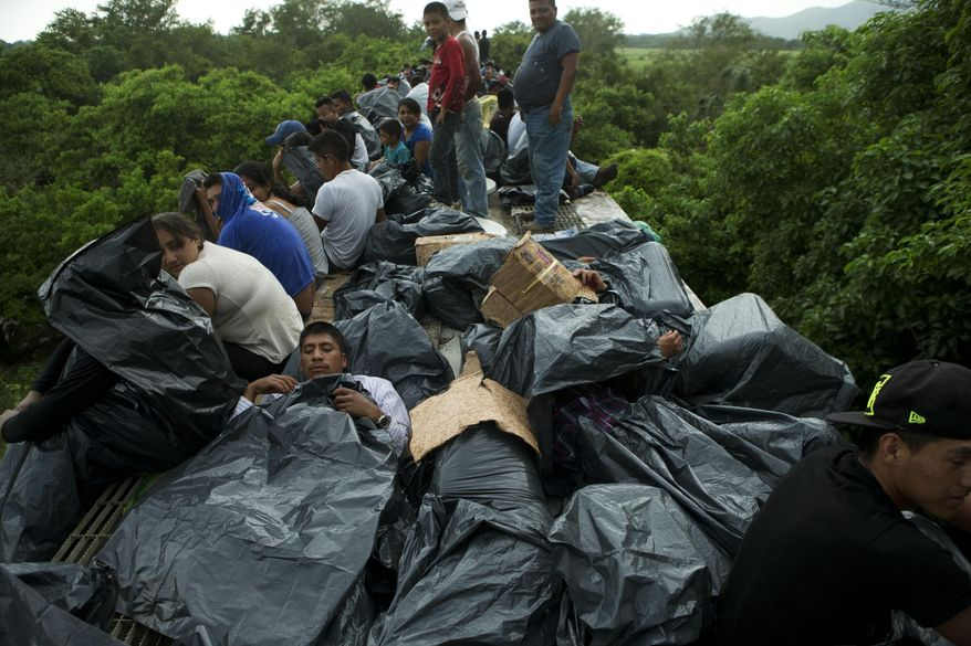 In this Friday, June 20, 2014 photo, Central American migrants use trash bags and cardboard to protect themselves from the rain as they wait atop a stuck freight train, outside Reforma de Pineda, Chiapas state, Mexico. The first leg of the long cross-country train journey, to Ixtepec in Oaxaca, typically takes 12-14 hours. On this occasion, the migrants had to endure alternate exposure to rain, cold, and heat for two full days, as the train suffered a minor derailment in a remote area halfway to Ixtepec. (AP Photo/Rebecca Blackwell)