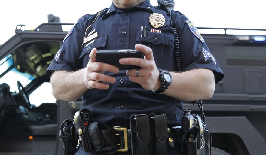 WEB STOCK Police Officer inspects a cell phone. (AP Photo)