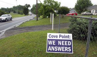 """Residents concerned about the Dominion Energy's Cove Point LNG Terminal express their dissatisfaction with signs in front of their homes along Cove Point Road, near the facility,  in Lusby, Md., Thursday, June 12, 2014. Federal regulators concluded that Dominion Energy's proposal to export liquefied natural gas from its Cove Point terminal on the Chesapeake Bay in Maryland would pose """"no significant impact"""" on the environment. (AP Photo/Cliff Owen)"""