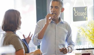 President Barack Obama, center, tastes some samples as he talks to owner of the Golden Fig Fine Food, Laurie Crowell, left, Thursday, June 26, 2014 in St. Paul, Minn. Crowell, wrote a letter to the Obama detailing the importance of mom and pop shops across the country and invited the President to drop by the shop if he was ever in the area. (AP Photo/Pablo Martinez Monsivais)