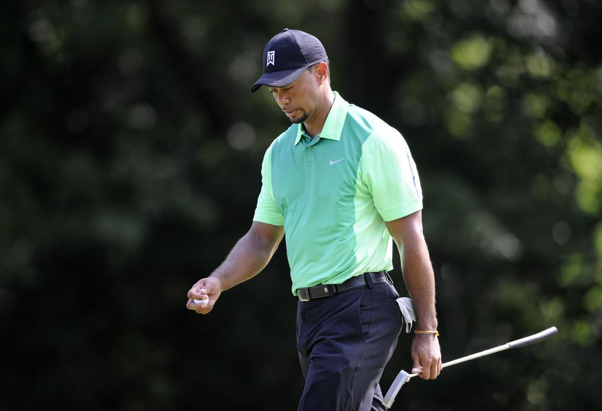 Tiger Woods walks off the 16th green during the first round of the Quicken Loans National golf tournament, Thursday, June 26, 2014, in Bethesda, Md. (AP Photo/Nick Wass)