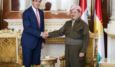 """Kurdish President Massoud Barzani, right, shakes hands for photographers with U.S. Secretary of State John Kerry at the presidential palace in Irbil on Tuesday, June 24, 2014. The president of Iraq's ethnic Kurdish region declared Tuesday that """"we are facing a new reality and a new Iraq"""" as the country's Shiite-led government considers new leadership as an immediate step to curb a Sunni insurgent rampage. The comments by Barzani came as he met with Kerry, who is pushing the central government in Baghdad to at least adopt new policies that would give more authorities to Iraq's minority Sunnis and Kurds.(AP Photo/ Brendan Smialowski, Pool)"""