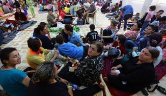 Iraqi Christian families, of those who fled from Mosul, Iraq, and other nearby towns, gather at a building of a social club in Ainkawa, a suburb of Irbil with a majority Christian population, Iraq, Thursday, June 26, 2014. Hundreds of Iraqi villagers fleeing advances by Sunni militants crowded at a checkpoint on the edge of the country's Kurdish-controlled territory Thursday seeking shelter in the relative safety of the self-rule region, as Britain's top diplomat arrived in Baghdad to urge the country's leaders to unite against the insurgent threat. (AP Photo)