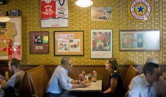 President Obama sits down to have lunch with Rebekah Erler at Matt's Bar in Minneapolis, Minnesota Thursday. Mr. Obama traveled to Minnesota to begin a two-day trip, where he plans to put a human face on the policies Democrats are championing. (ASSOCIATED PRESS)
