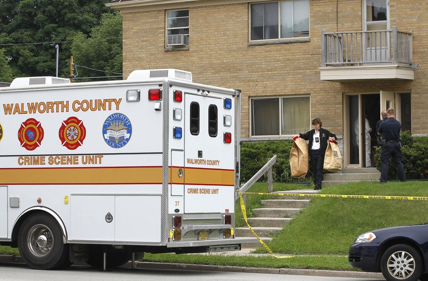 In this photo taken on Wednesday, June 25, 2014, Walworth County investigators carry bags full of material from an apartment in West Allis, Wis., after picking up a suspect allegedly involved in two murders where the bodies were found in suitcases along a rural road in Geneva Township several weeks ago. (AP Photo/Milwaukee Journal-Sentinel, Gary Porter)
