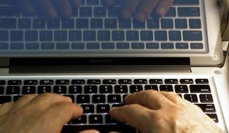 In this Feb. 27, 2013, photo illustration, hands type on a computer keyboard in Los Angeles. (AP Photo/Damian Dovarganes, File)