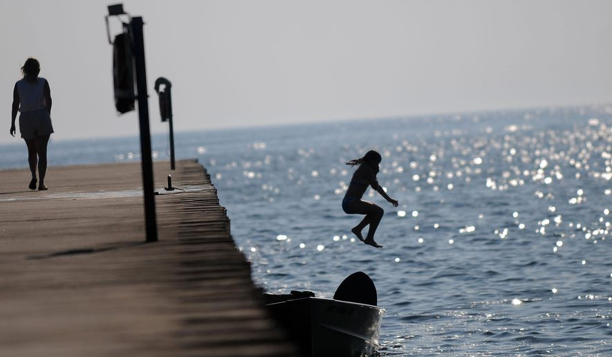 """A young swimmer jumps into Lake Michigan off of the pier in Montegue, Mich. White Lake in Muskegon County was declared a Great Lakes """"area of concern"""" in 1985 because of severe environmental degradation, primarily from industrial and municipal wastes. (AP Photo/Detroit News, Elizabeth Conley)"""