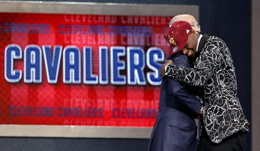 Andrew Wiggins of Kansas, hugs NBA commissioner Adam Silver after being selected by the Cleveland Cavaliers as the number one pick in the 2014 NBA draft, Thursday, June 26, 2014, in New York.  (AP Photo/Kathy Willens)