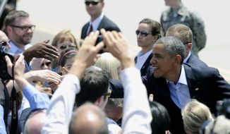 President Barack Obama greets members of the military and their families as he arrives in St. Paul, Minn., Thursday, June 26, 2014. Obama traveled to Minnesota to begin a two-day trip, where he plans to put a human face on the economic policies he and Democrats are championing, and is meeting with Erler, who wrote the White House about her struggles to make ends meet. (AP Photo/Hannah Foslien)