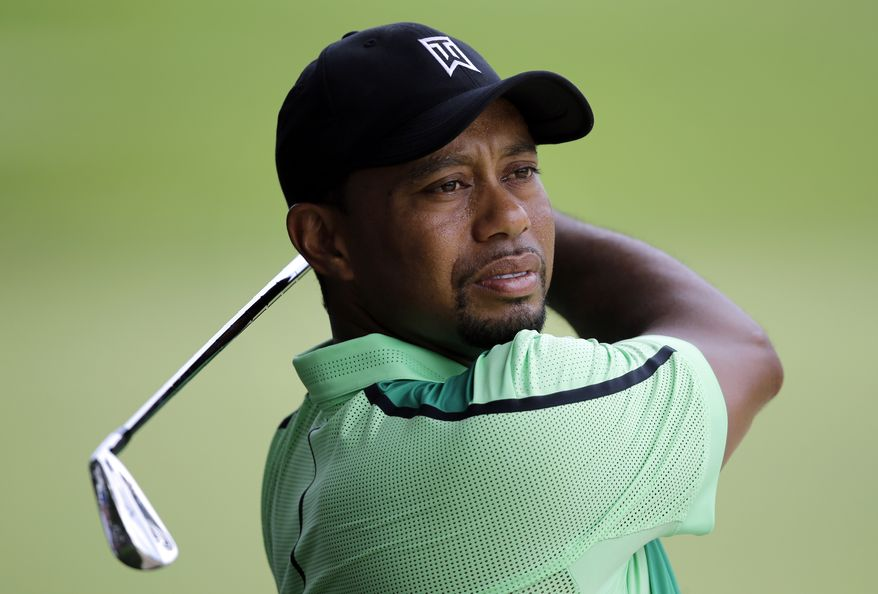 Tiger Woods takes a practice swing before hitting out of a sand trap on the ninth fairway during the first round of the Quicken Loans National PGA golf tournament, Thursday, June 26, 2014, in Bethesda, Md. (AP Photo/Patrick Semansky)