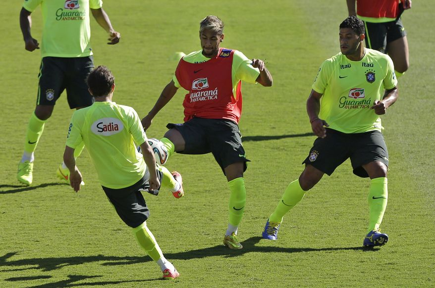 Brazil's Neymar, center, practices with Hulk, right, and Bernard during a training session one day before their team's round of 16 World Cup soccer match with Chile at Mineirao Stadium in Belo Horizonte, Brazil, Friday, June 27, 2014. (AP Photo/Andre Penner)