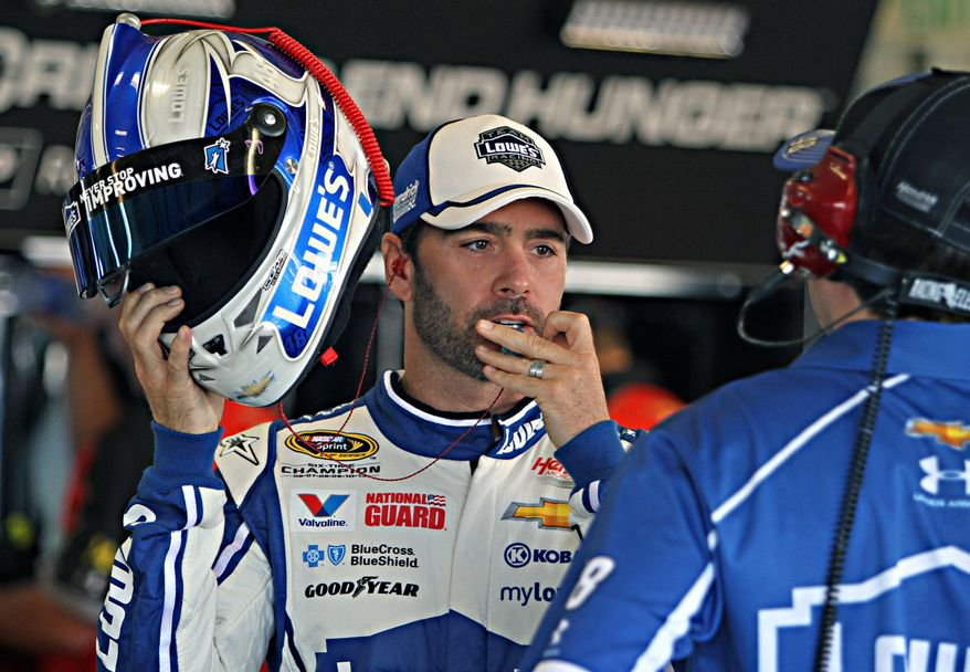 NASCAR driver Jimmie Johnson, left, talks with crew chief Chip Knaus, right, before the start of a practice session at Kentucky Speedway in Sparta, Ky., Friday June 27, 2014. The NASCAR Kentucky auto race will be Saturday night. (AP Photo/Garry Jones)