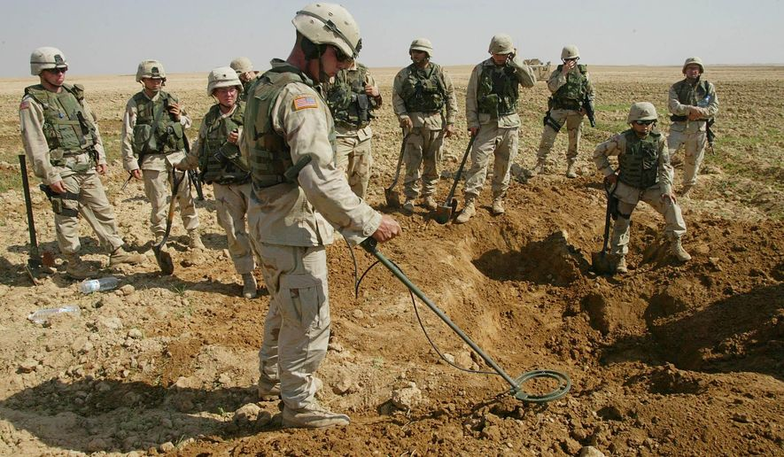 This Oct. 9, 2003, photo shows soldiers from the U.S. Army's 720th Military Police Battalion watching as a minesweeper looks for weapons in a hole they dug during a raid on a farmland just outside Tikrit, Iraq. (Associated Press) **FILE**