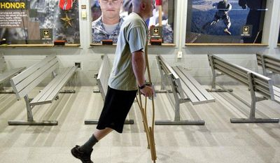 ** FILE ** U.S. Army Sgt. Josh Olson enters the indoor shooting range for practice at Fort Benning, Ga., May 30, 2012. Olson was on a routine patrol in Tal Afar, Iraq, when a grenade that was lobbed at his Humvee exploded. He lost his right leg in the attack, and would end up spending 18 months at the Walter Reed National Military Medical Center. (AP Photo/David Goldman, File)