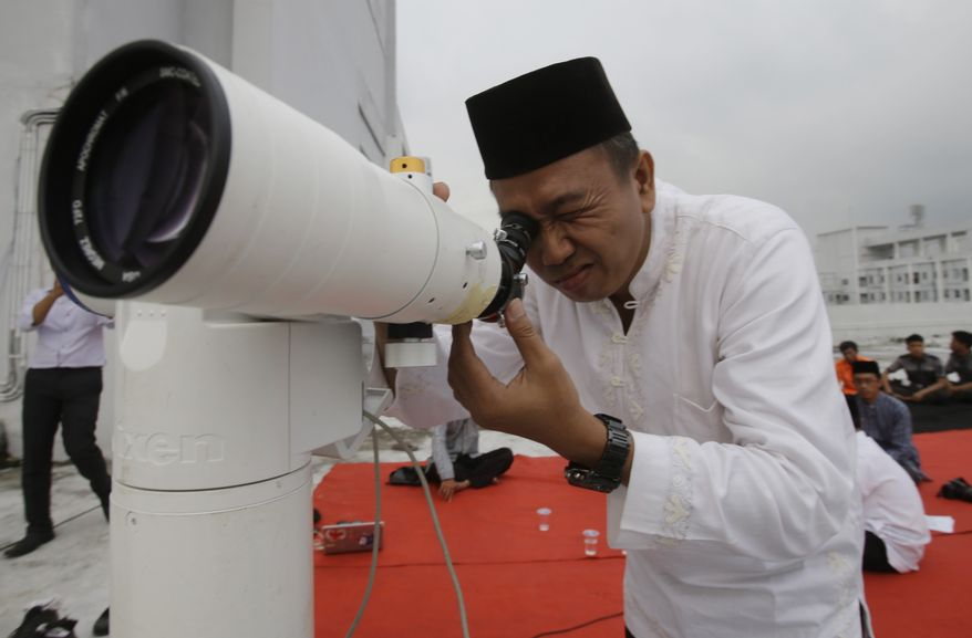 Muslim clerics scan the horizon for the crescent moon that will determine the beginning of the holy fasting month of Ramadan in Jakarta, Indonesia,Friday, June 27, 2014. Muslims around the world will start observing Ramadan, the holiest month in Islamic calendar this week. (AP Photo/Achmad Ibrahim)