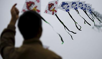 Xian Lin, of Potomac, Md., flies his kite during the annual kite festival on the National Mall, in Washington, Sunday, April 10, 2011. On his kite were the mascots from the Beijing 2008 Olympic Games. (Drew Angerer/The Washington Times)