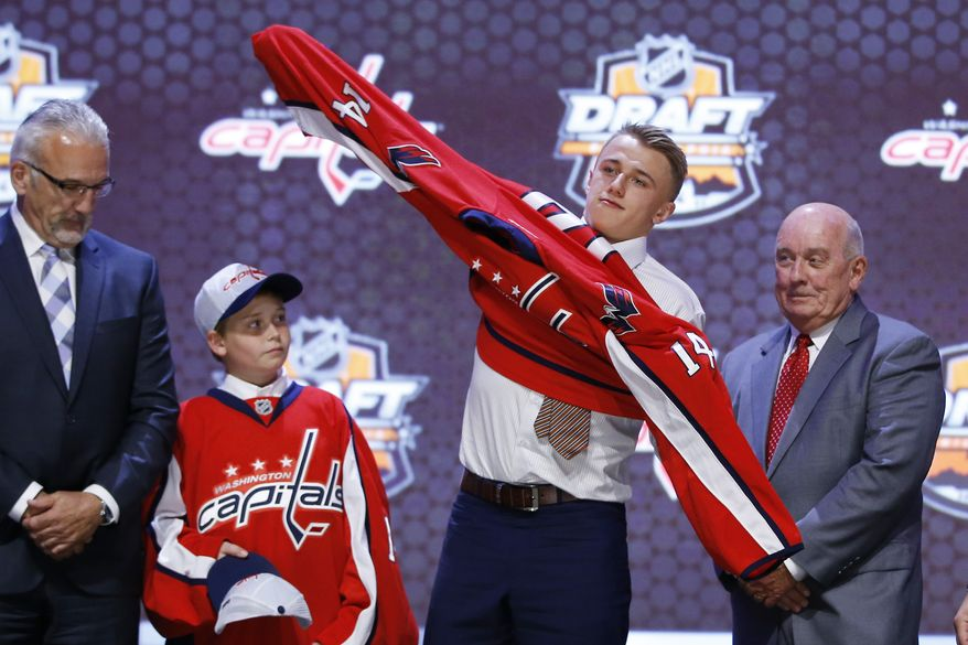 Jakub Vrana pulls on a Washington Capitals sweater after being chosen 13th overall during the first round of the NHL hockey draft, Friday, June 27, 2014, in Philadelphia. (AP Photo/Matt Slocum)