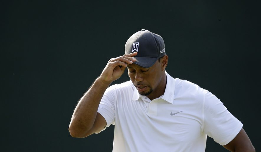 Tiger Woods removes his cap after finishing the second round of the Quicken Loans National PGA golf tournament, Friday, June 27, 2014, in Bethesda, Md. Woods ended the day at 7 over par for the tournament and missed the cut. (AP Photo/Patrick Semansky)