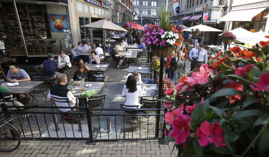 **FILE** This Thursday, June 26, 2014 photo shows restaurant patrons enjoying outdoor dining on East 4th Street in Cleveland. (AP Photo/Tony Dejak)
