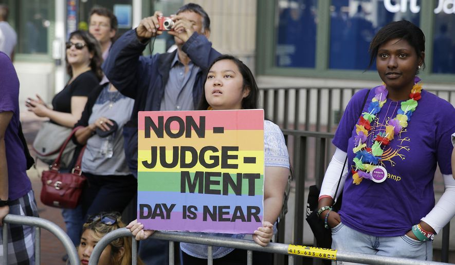 Eliza Galimba, 16, holds up a sign while watching the 44th annual San Francisco Gay Pride parade Sunday, June 29, 2014, in San Francisco. The lesbian, gay, bisexual, and transgender celebration and parade is one of the largest LGBT gatherings in the nation. (AP Photo/Eric Risberg)