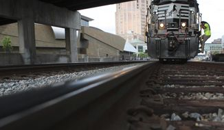 "FOR RELEASE SUNDAY, JUNE 29, 2014, AT 9:00 A.M. EDT.  This photo taken June 13, 2014, shows Tim Tucker, a conductor with Norfolk Southern based out of Lynchburg, climbing down from the locomotive cab to do a final check before departing from downtown Roanoke, Va., for the Appalachian whistle-stop Safety Train. ""A lot of people, they want to get on the tracks and they think trains can just stop on a dime but trains can't stop. You shouldn't cross tracks but if you have to, make sure to look both ways, make sure everything is clear,"" Tucker said. Tucker also mentioned to call the number on the back of the stop sign to report any sightings of cars parked near the tracks. Norfolk Southern and Virginia Operation Lifesaver operated across 364 miles of Norfolk Southern's railroad, stopping in nine cities on its way from Cleveland, Tenn., to Lynchburg, Va., June 9-13. The trip was aimed to raise public awareness about being safe and to stay alert at highway/rail crossings around railroad tracks. (AP Photo/The Roanoke Times, Erica Yoon)"