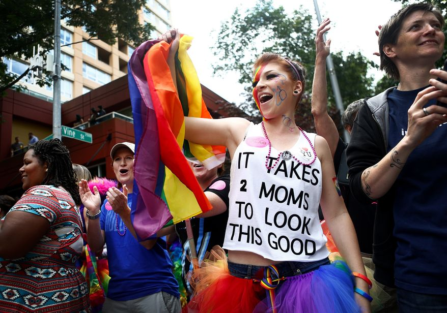 "** FILE ** Laura Taylor, attends the pride parade with her parents Kelle Taylor, in blue, and Stephanie Taylor, center, in black, and waves a rainbow flag as she watches floats go by on 4th Avenue and Vine Street during the 40th annual Seattle Pride Parade on Sunday, June 29, 2014. This year's theme was ""Generations of Pride,"" to honor those who ""fought the early battles"" and who are ""continuing to advocate for equality in changing times."" (AP Photo/The Seattle Times, Lindset Wasson)"