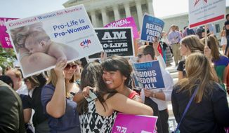 Demonstrators embrace as they react to hearing the Supreme Court's decision on the Hobby Lobby case outside the Supreme Court in Washington, Monday, June 30, 2014. The Supreme Court says corporations can hold religious objections that allow them to opt out of the new health law requirement that they cover contraceptives for women.(AP Photo/Pablo Martinez Monsivais)
