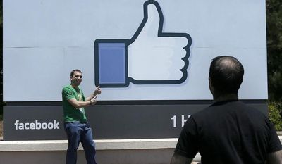 ** FILE ** In this June 11, 2014, photo, a man poses for photographs in front of the sign at the Facebook campus in Menlo Park, Calif. (AP Photo/Jeff Chiu)