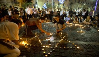 Israelis light candles as they gather in Jerusalem after the announcement that the bodies of the three missing teenagers were found near the West Bank town of Hebron, late Monday, June 30, 2014. The Israeli military found the bodies of three missing teenagers on Monday, just over two weeks after they were abducted in the West Bank, allegedly by Hamas militants. The grisly discovery culminated a feverish search that led to Israel's largest ground operation in the Palestinian territory in nearly a decade and raised fears of renewed fighting with Hamas. Israeli Prime Minister Benjamin Netanyahu was huddling with his Security Cabinet late Monday to discuss a response. (AP Photo/Sebastian Scheiner)