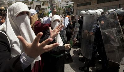 Supporters of Hamas against a recent arrest of Palestinians in Israeli raids confront Palestinian police officers during a protest in the West Bank city of Hebron, Friday, June 20, 2014. (AP Photo/Majdi Mohammed)