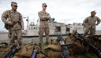In this file photo, U.S. Marines prepare to board the U.S. Navy LCAC (Landing Craft Air Cushion) vehicle following the joint U.S.-Philippines naval exercise, dubbed Cooperation Afloat Readiness and Training (CARAT), Monday, June 30, 2014 at the Naval Education and Training Center at San Antonio township, Zambales province in northwestern Philippines.  (AP Photo/Bullit Marquez) **FILE**