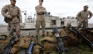U.S. Marines prepare to board the U.S. Navy LCAC (Landing Craft Air Cushion) vehicle following the joint U.S.-Philippines naval exercise, dubbed Cooperation Afloat Readiness and Training (CARAT), Monday, June 30, 2014 at the Naval Education and Training Center at San Antonio township, Zambales province in northwestern Philippines. More than 100 Filipino and U.S. Marines in assault amphibious vehicles conducted a mock assault on imaginary enemies in military drills Monday on a beach in northwestern Philippines fronting the South China Sea, where Manila is locked in a territorial dispute with China. (AP Photo/Bullit Marquez)