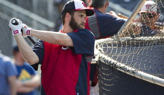 Washington Nationals outfielder Bryce Harper warms up during batting practice before the start of a baseball game against the Colorado Rockies at Nationals Park, on Monday, June 30, 2014, in Washington. Harper is returning to the lineup after missing 59 games with a torn ulnar collateral ligament in his left thumb. (AP Photo/ Evan Vucci)
