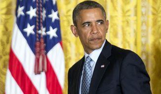 ** FILE ** President Obama walks across the East Room of the White House in Washington, Monday, June 30, 2014. (AP Photo/Manuel Balce Ceneta)