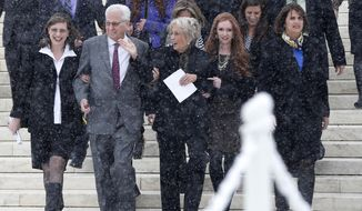 FILE - In this March 25, 2014 file photo, David Green, founder and chief executive officer of Hobby Lobby, second from left, walks with his wife Barbara, center, and members of their family as they acknowledge a cheer from demonstrators in the crowd as they descend the steps of the Supreme Court in Washington. The Monday, June 30, 2014 Supreme Court ruling that the Hobby Lobby crafts store chain does not have to provide all forms of birth control marks the first time the high court has said some businesses can hold religious views under federal law, in cases where there is essentially no difference between the business and its owners. (AP Photo/Charles Dharapak, File)