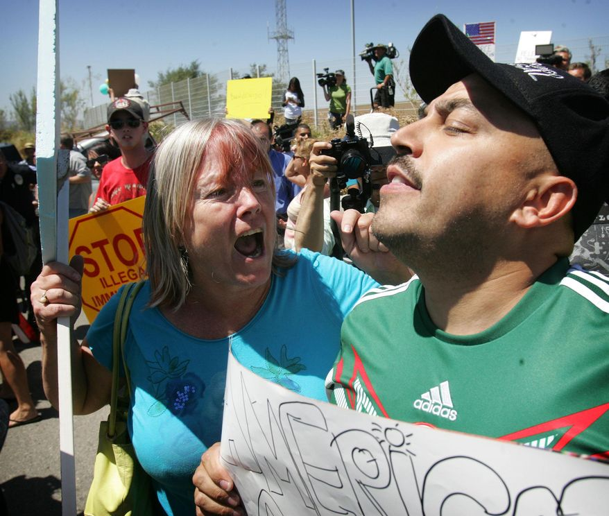 An unidentified protester, left, argues with American citizen Lupillo Rivera, brother of Mexican-American singer Jenni Rivera, right, as three buses carrying 140 immigrants attempt to enter the Murrieta U.S. Border Patrol station for processing on Tuesday, July 1, 2014.  (AP Photo/The Press-Enterprise, )  MAGS OUT; MANDATORY CREDIT
